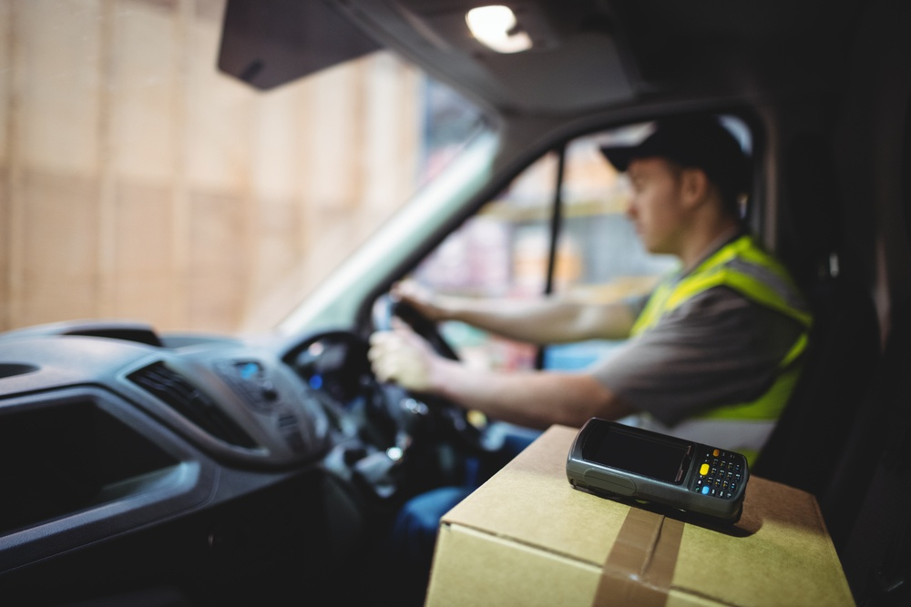Delivery driver driving van with parcels on seat outside warehouse-4