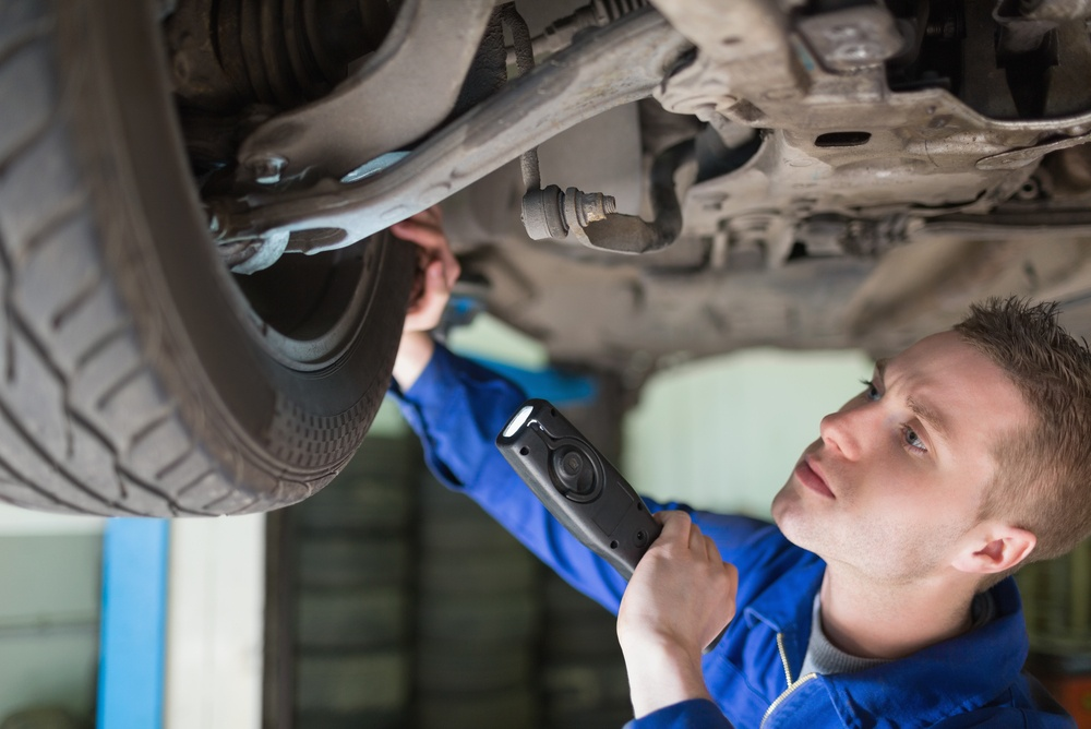 Male mechanic with flashlight examining tire