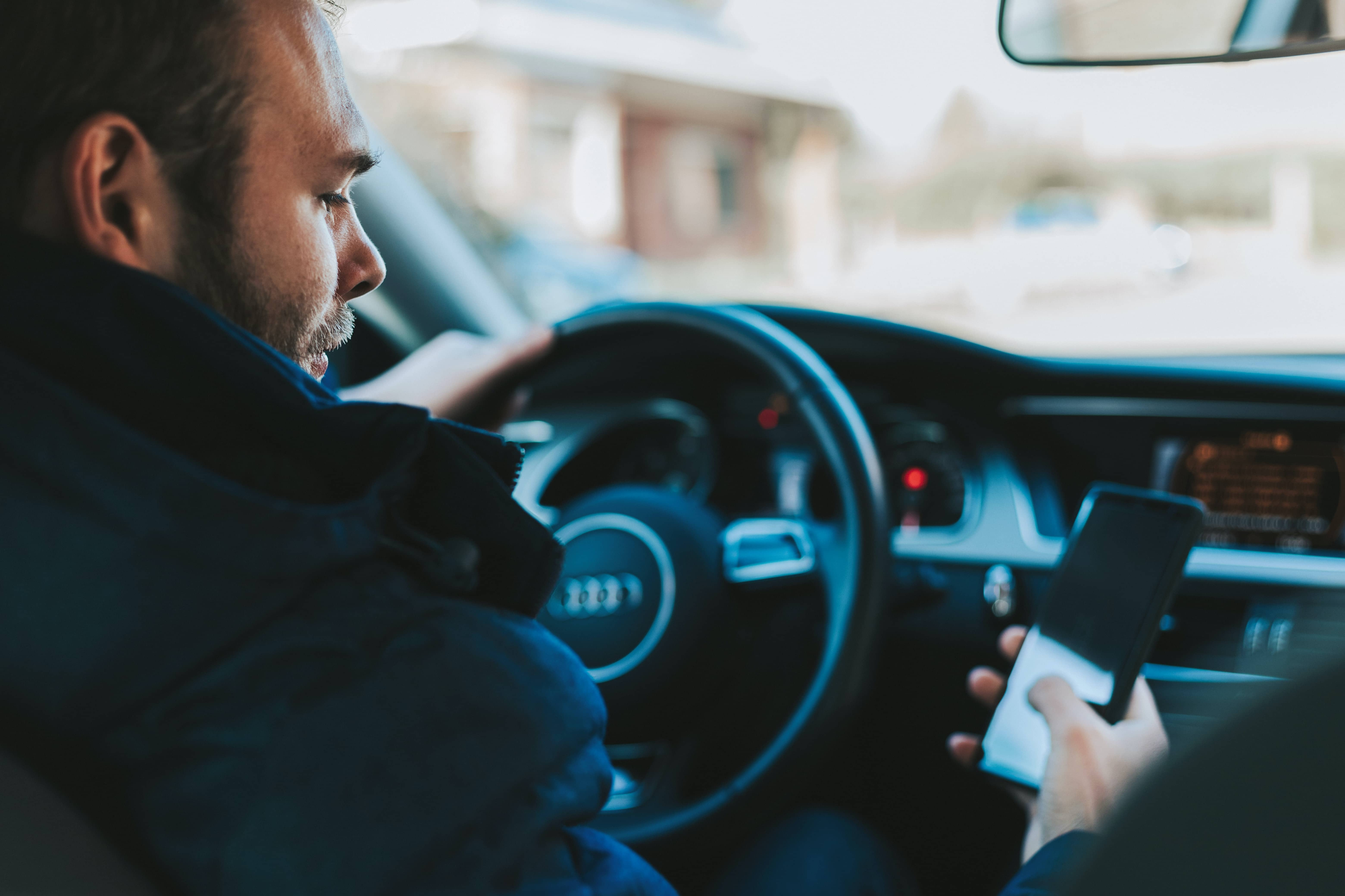 Man driving car on his phone.