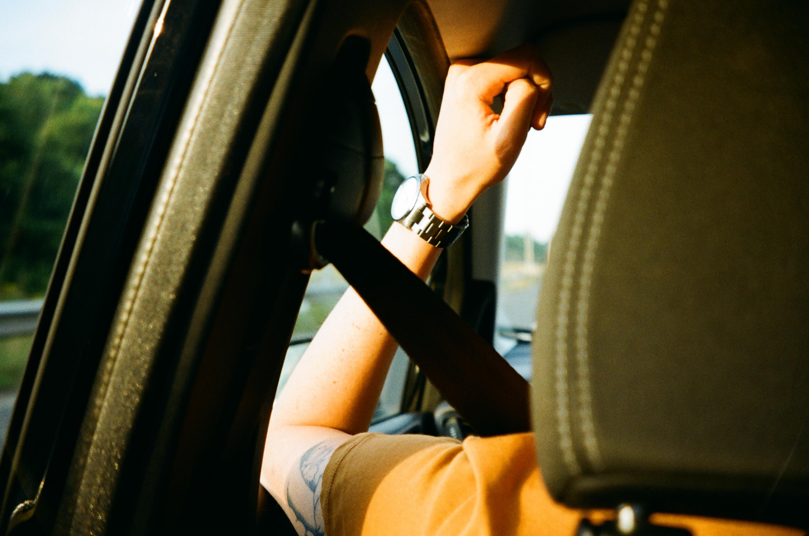 Passenger sitting in car with seatbelt on.
